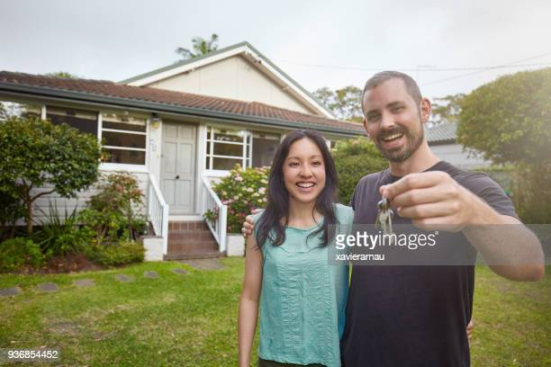 happy mixed-race couple showing the keys of the new house - home ownership stock pictures, royalty-free photos & images