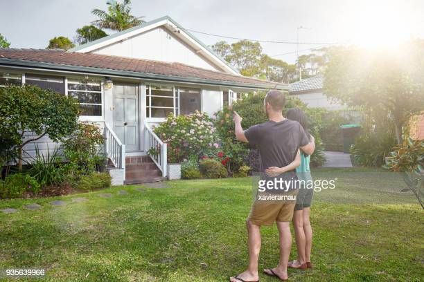 Happy mixed-race couple standing in front of house