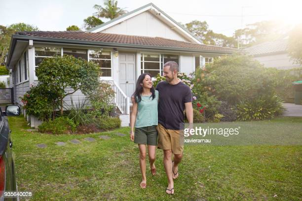 Happy mixed-race couple walking outside their front yard garden