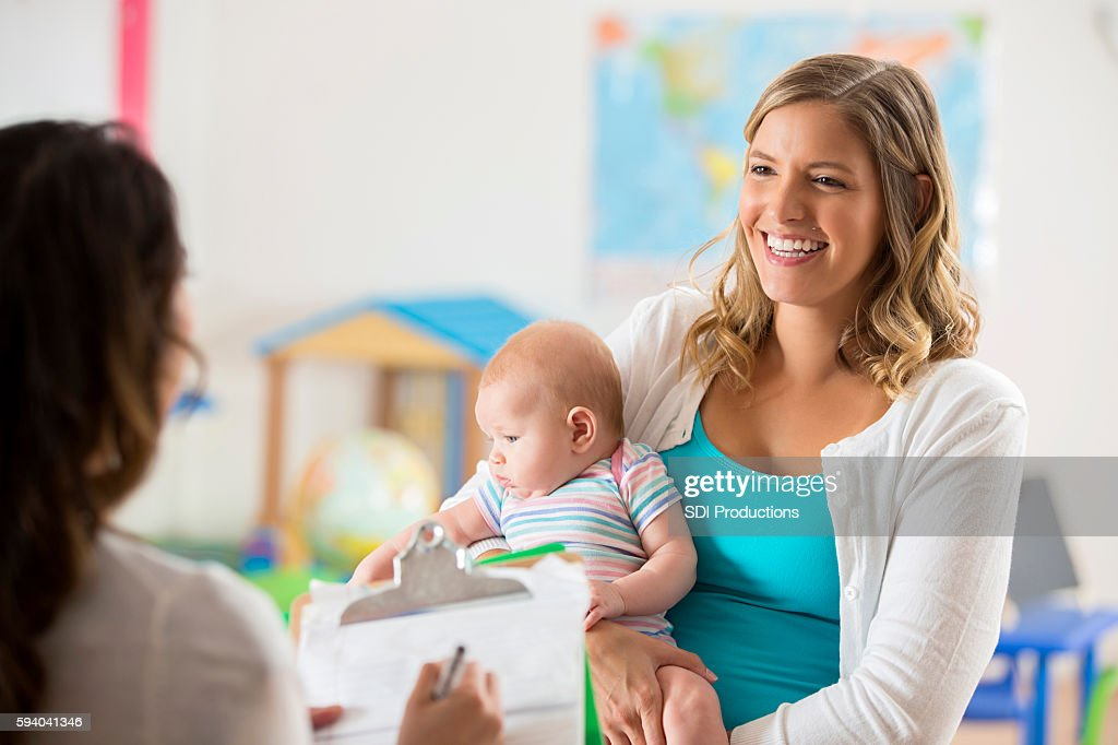 Happy mom and baby getting tour of a daycare center : Stock Photo
