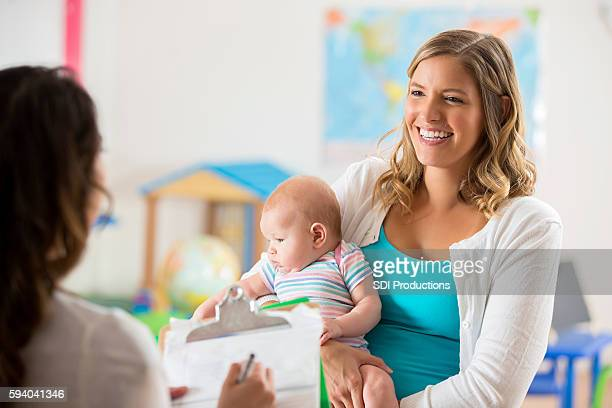 Happy mom and baby getting tour of a daycare center