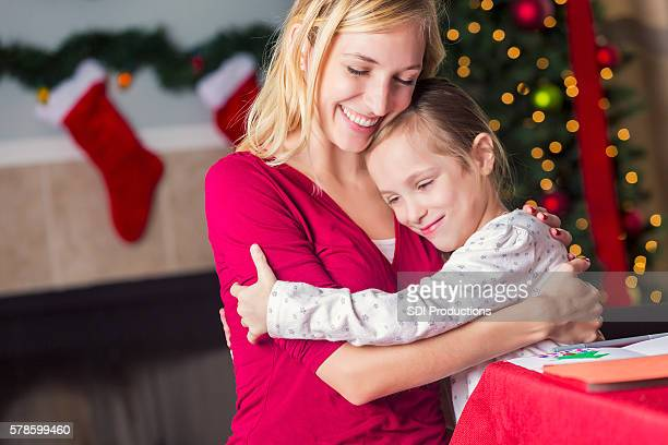 Happy mom and daughter hugging each other during Christmas