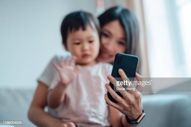 happy mom and daughter on a video call with smartphone - zwaaien gebaren stockfoto's en -beelden