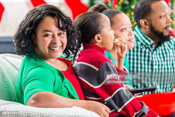 Happy mom enjoys movie with family at Christmastime
