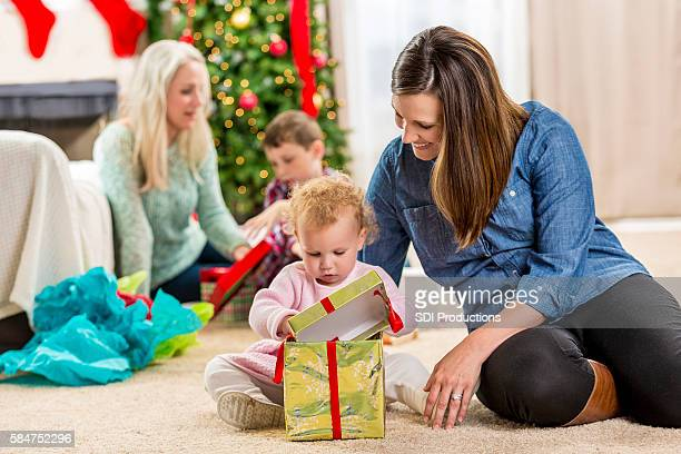 Happy mom opens gifts with children on Christmas morning