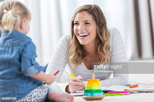 Happy mom plays with toddler daughter at home