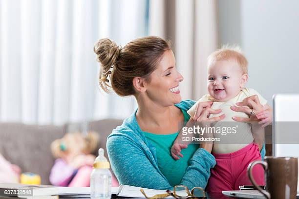 Happy mom smiles at baby girl