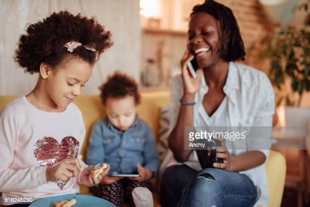 彼女の子供が朝食を食べている間に、電話で話す幸せママ - interracial cartoon ストックフォトと画像