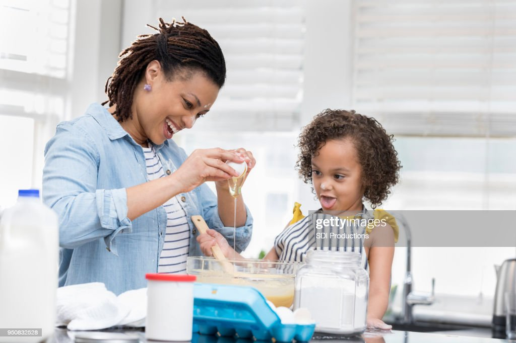 Happy Mom Teaches Young Daughter To Bake Stock Photo