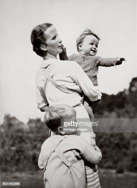 A Happy Mother a National Socialist Ideal' Germany 1936 A picture of a mother carrying a smiling baby with another child hugging her A portrait of a...