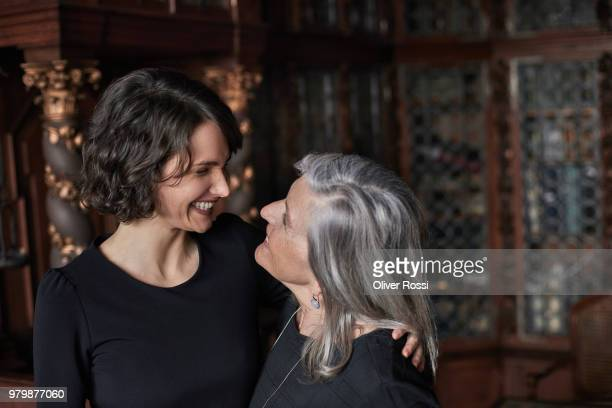 happy mother and adult daughter smiling at each other - só adultos imagens e fotografias de stock