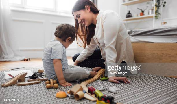 Happy mother and baby boy playing with toys on rug at home
