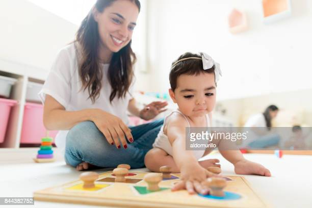 happy mother and baby daughter playing at home - mexican mom stock photos and pictures