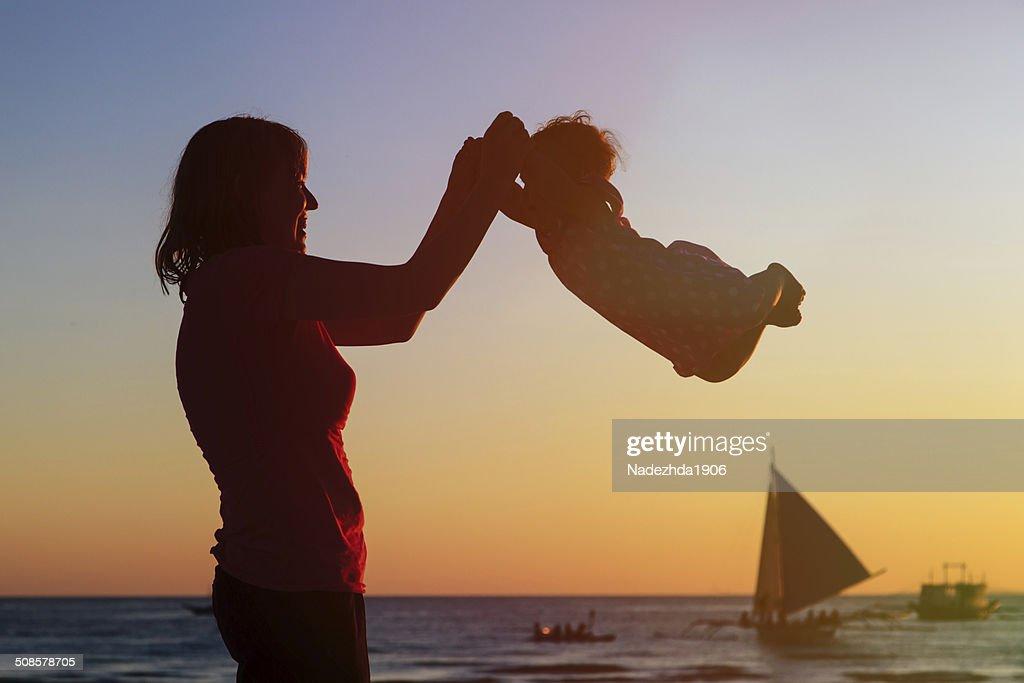 Glückliche Mutter und baby Spaß am sunset beach : Stock-Foto