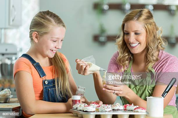 Happy mother and child decorate cupcakes