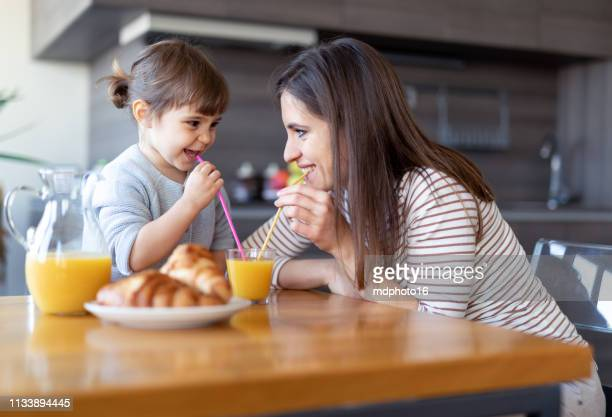 happy mother and daughter drinking juice together - orange juice stock pictures, royalty-free photos & images