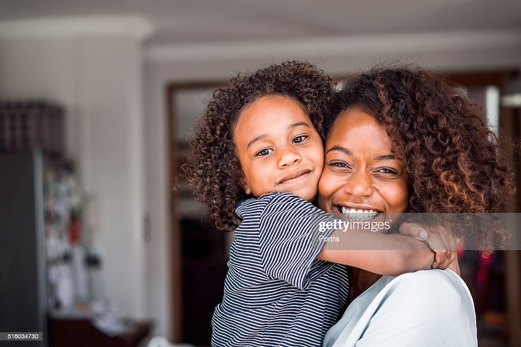 Happy mother and daughter embracing at home : Stock Photo