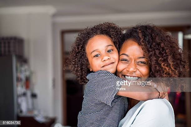 Happy mother and daughter embracing at home