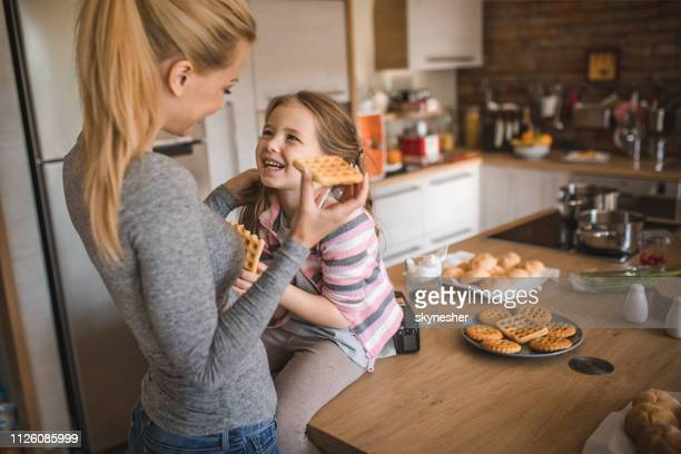 happy mother and daughter enjoying in homemade waffles at home. - cream cake stock pictures, royalty-free photos & images