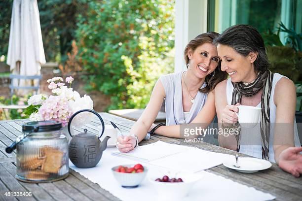 Happy mother and daughter having tea outdoor