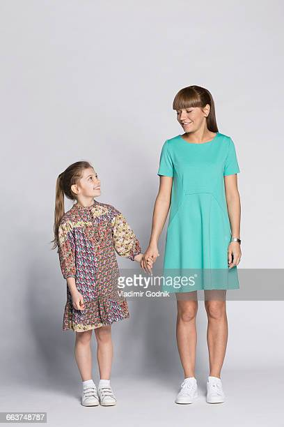 Happy mother and daughter holding hands against white background