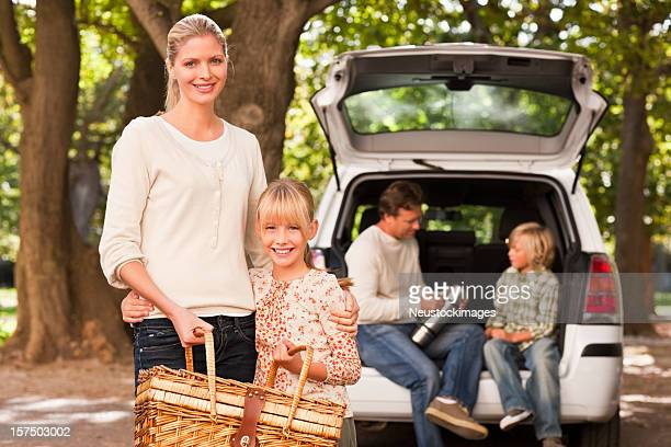 Happy mother and daughter holding picnic basket