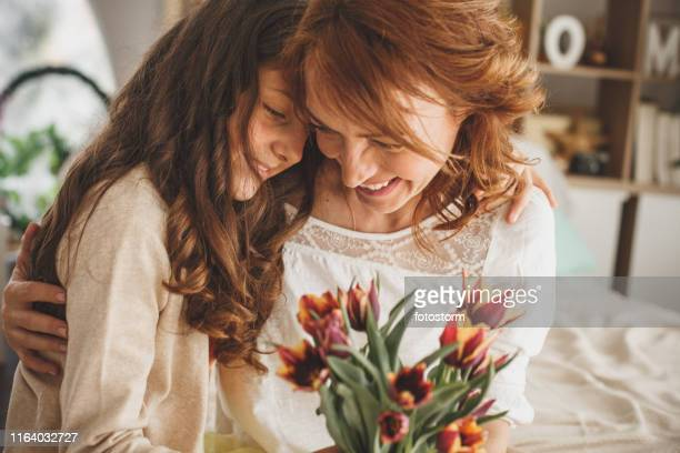 happy mother and daughter hugging and holding a bouquet of fresh flowers - mother's day stock pictures, royalty-free photos & images