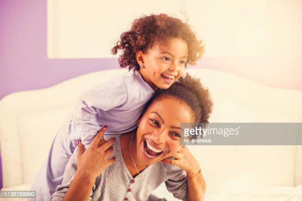 happy mother and daughter in bed - black mothers day stock pictures, royalty-free photos & images
