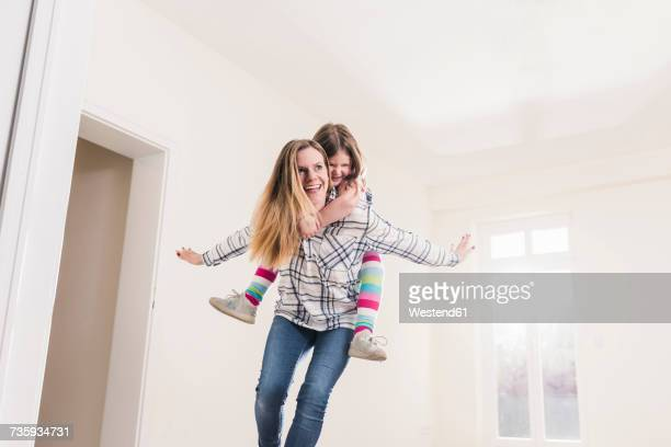 happy mother and daughter in empty apartment - piggyback stock pictures, royalty-free photos & images