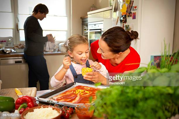 Happy mother and daughter in kitchen preparing pizza with father in background