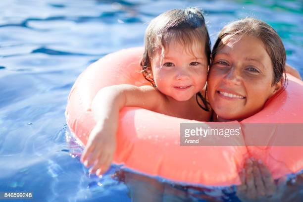 happy mother and daughter in swimming pool - hot mom stock photos and pictures
