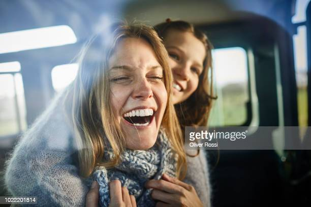 happy mother and daughter inside off-road vehicle - ungestellt stock-fotos und bilder