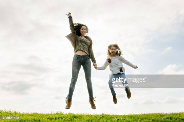 Happy mother and daughter jumping on a meadow