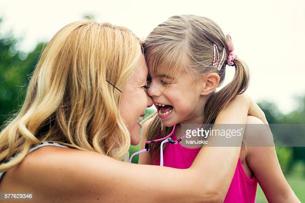 Happy mother and daughter laughing outdoors