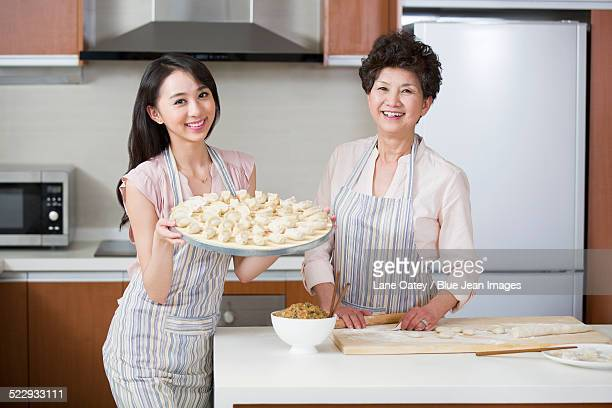 Happy mother and daughter making dumplings