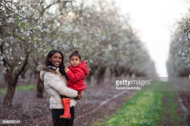 Heureuse mère et fille sur le champ d'amandiers au printemps.