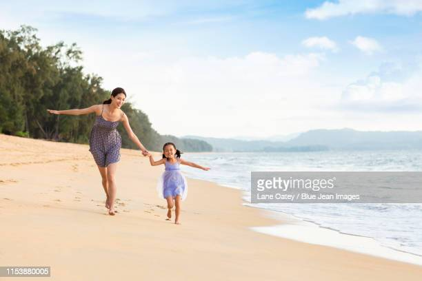 happy mother and daughter on beach - superman stock pictures, royalty-free photos & images