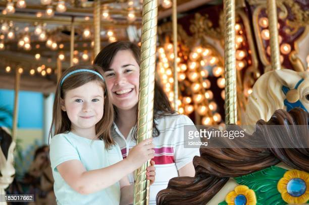 Glückliche Mutter und Tochter auf Karussell Horse