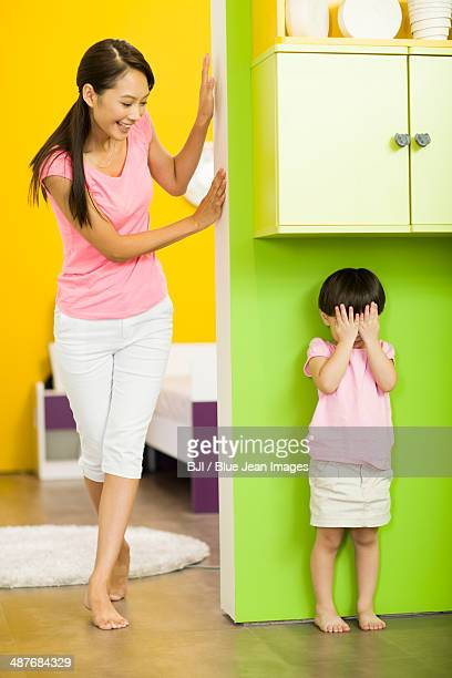 Happy mother and daughter playing hide and seek