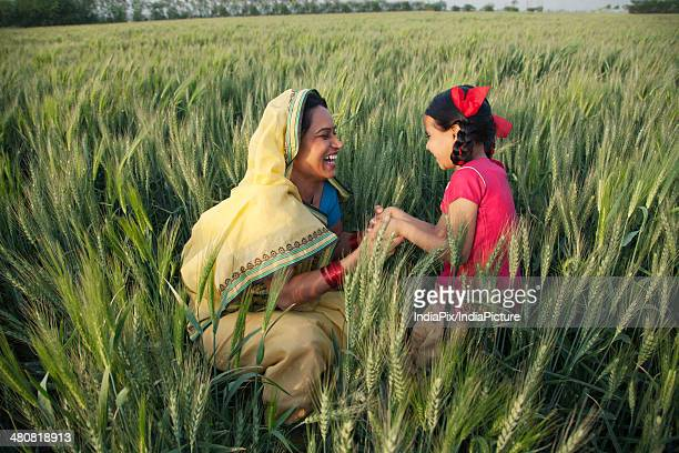 Happy mother and daughter playing in farm