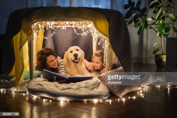 happy mother and daughter relaxing with a dog in a tent and reading a book. - one animal stock pictures, royalty-free photos & images