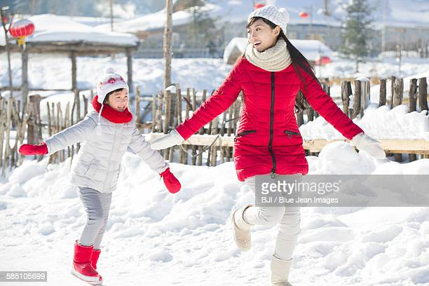 Happy mother and daughter running in the snow