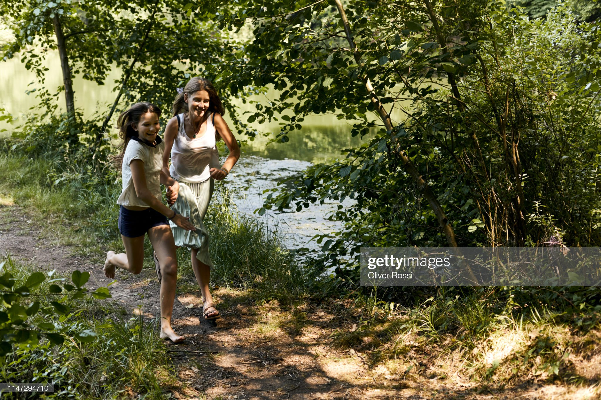 https://media.gettyimages.com/photos/happy-mother-and-daughter-running-on-path-at-a-pond-picture-id1147294710?s=2048x2048