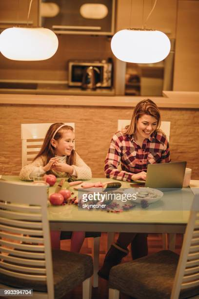 Happy mother and daughter searching for recipes on the Internet.