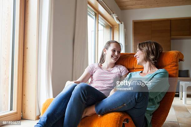 Happy mother and daughter sitting in armchair at home
