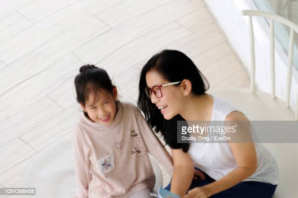 Happy Mother And Daughter Sitting On Chairs