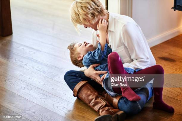 Happy mother and daughter sitting on the floor at home