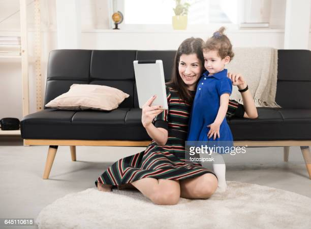 Happy mother and daughter taking selfie with digital tablet at home