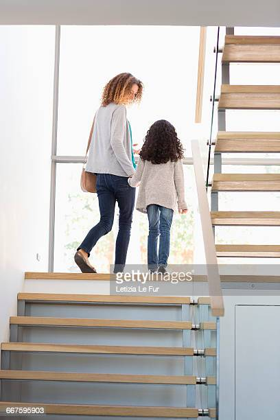 Happy mother and daughter talking on staircase