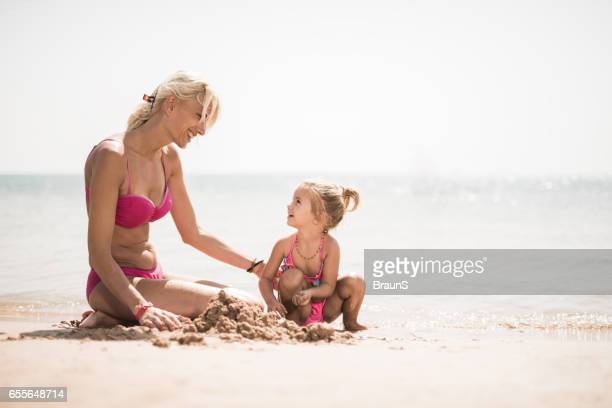 Happy mother and daughter talking on the beach.